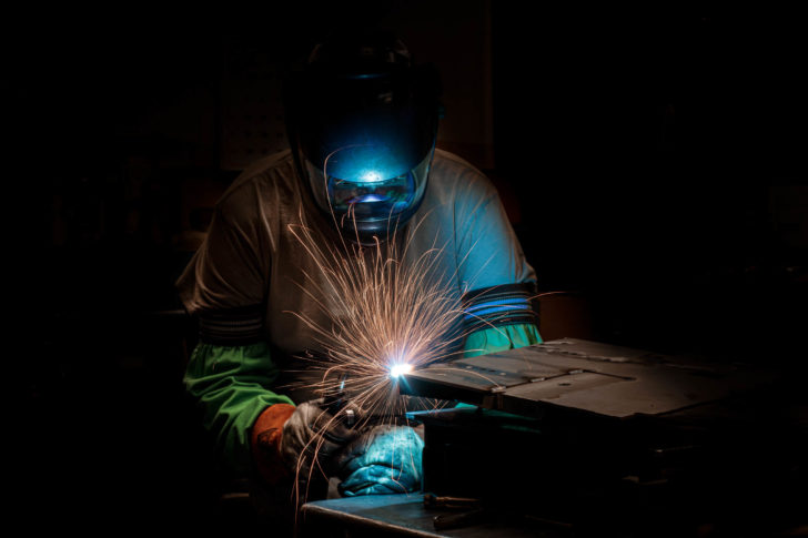 Dawson worker in protective gear welding metal