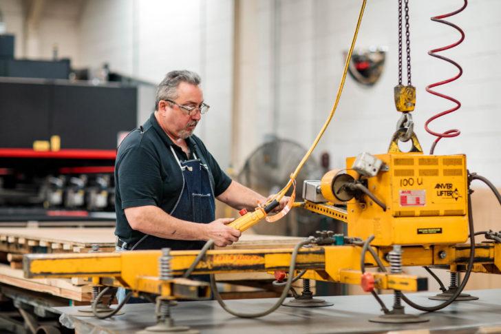 Dawson worker loading sheet metal onto a laser